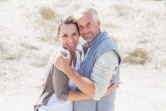 Happy couple hugging on the beach looking at camera Royalty Free Stock Image