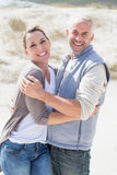 Happy couple hugging on the beach looking at camera Stock Photo