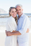 Happy couple hugging on the beach looking at camera Stock Photography