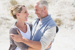 Happy couple hugging on the beach looking at each other Stock Photo