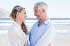 Happy couple hugging on the beach looking at each other Royalty Free Stock Photography