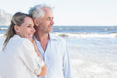 Happy couple hugging on the beach looking out to sea Stock Images