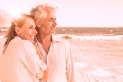 Happy couple hugging on the beach looking out to sea Royalty Free Stock Photos