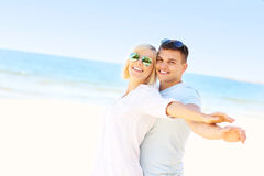 Happy couple hugging at the beach. A picture of a young romantic couple hugging at the beach Stock Image