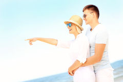 Happy couple hugging at the beach and pointing Royalty Free Stock Photo