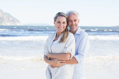 Happy couple hugging on the beach woman looking at camera. Happy couple hugging on the beach women looking at camera on a sunny day Royalty Free Stock Photos