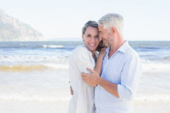 Happy couple hugging on the beach woman looking at camera Stock Photography