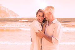 Happy couple hugging on the beach woman looking at camera Stock Photos