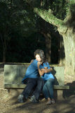 Happy Couple Hugging on a Bench - Vertical Stock Photo