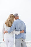 Happy couple hugging each other and looking at the sea Stock Image