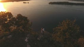 Happy couple hugging at the edge of the cliff, aerial shoting stock footage