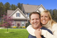 Happy Couple Hugging in Front of House Royalty Free Stock Photo