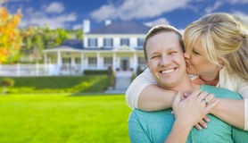 Happy Couple Hugging In Front of House Stock Photo