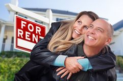 Happy Couple Hugging in Front of For Rent Real Estate Sign and Home. Happy Couple Hugging in Front of For Rent Real Estate Sign and House royalty free stock image