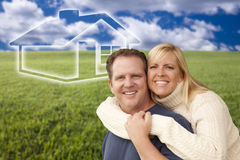 Happy Couple Hugging in Grass Field with Ghosted House Behind Stock Photos