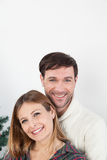 Happy couple hugging himself beside the christmas tree Stock Photography