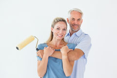 Happy couple hugging and holding paint roller Stock Photography