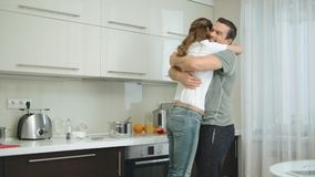 Joyful couple hugging each other at kitchen. Happy husband twisting smiling wife