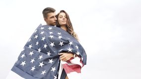 Happy couple hugging and kissing wrapped in an American flag in nature. Independence Day, lifestyle, travel concept. Happy couple hugging and kissing wrapped in stock footage