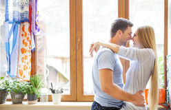 Happy couple hugging in the kitchen Stock Photos
