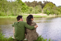 Happy couple hugging on lake or river bank Royalty Free Stock Image