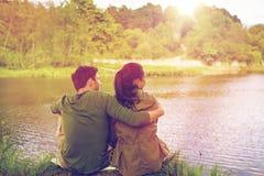 Happy couple hugging on lake or river bank Stock Photo