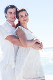 Happy couple hugging and looking at camera Stock Photo