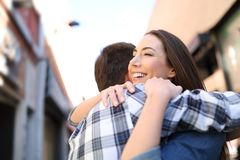 Happy couple hugging after meeting in the street stock photography