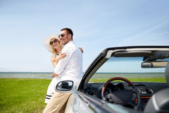 Happy couple hugging near cabriolet car at sea royalty free stock images
