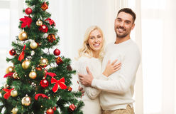 Happy couple hugging near christmas tree at home Stock Photos