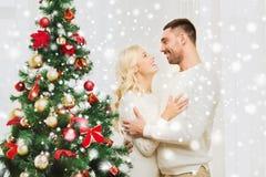 Happy couple hugging near christmas tree at home Stock Photos