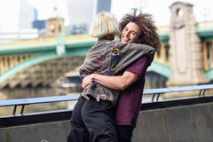 Happy couple hugging near the Southwark bridge over River Thames, London. UK royalty free stock photo