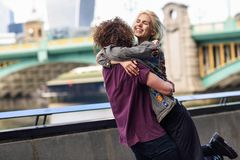Happy couple hugging near the Southwark bridge over River Thames, London. UK royalty free stock image