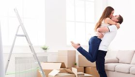 Happy couple hugging near unpacked boxes Stock Image