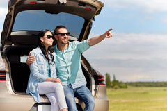Happy couple hugging at open hatchback car trunk Stock Photo