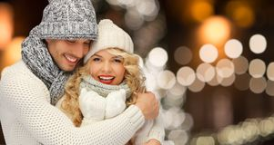 Happy couple hugging over christmas lights Royalty Free Stock Images