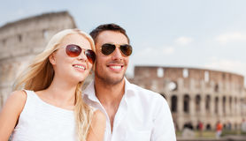 Happy couple hugging over coliseum. Summer holidays, travel, tourism, people and dating concept - happy couple hugging over coliseum background Royalty Free Stock Photo