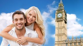 Happy couple hugging over london big ben tower. Summer holidays, travel, tourism, people and dating concept - happy couple hugging over london big ben tower Stock Photos
