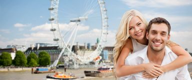 Happy couple hugging over london ferry wheel. Summer holidays, travel, tourism, people and dating concept - happy couple hugging over london ferry wheel Royalty Free Stock Image