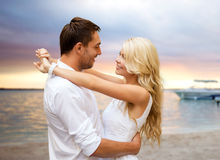 Happy couple hugging over sunset beach background Royalty Free Stock Images