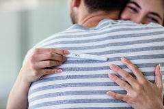 Happy couple hugging with positive pregnancy test Stock Photos