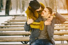 Happy couple walking through the park on a sunny winter day. Happy couple hugging and sitting on a bench in the park on a sunny winter day Stock Photo