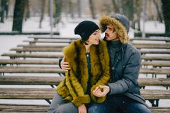 Happy couple walking through the park on a sunny winter day. Happy couple hugging and sitting on a bench in the park on a sunny winter day Stock Photography