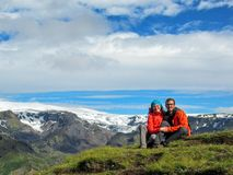 Happy couple hugging sitting on the stone in the icelandic highlands and admire the scenery view with highland mountains, glaciers royalty free stock photo