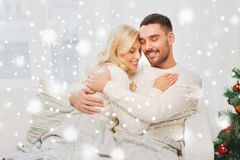 Happy couple hugging on sofa at home Stock Images