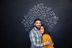 Happy couple hugging and standing over black board. Happy young couple hugging and standing over black board behind them stock image