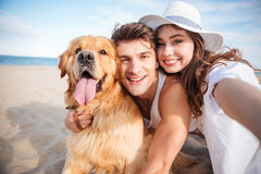 Happy couple hugging their dog and smiling on the beach Stock Photos