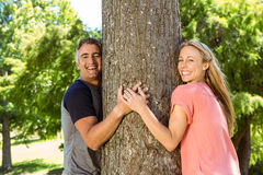 Happy couple hugging a tree Royalty Free Stock Photography