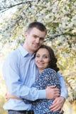 Happy couple hugging under spring tree stock photo