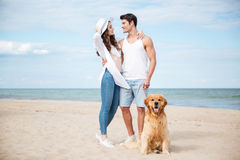 Happy couple hugging while walking with dog on the beach. Happy young couple hugging and smiling while walking with dog on the beach Royalty Free Stock Photo